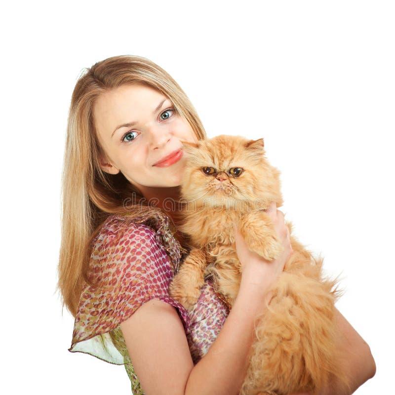 La gentille fille avec un chat rouge sur des mains photographie stock libre de droits