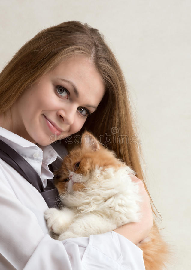 La gentille fille avec un chat rouge sur des mains photo stock