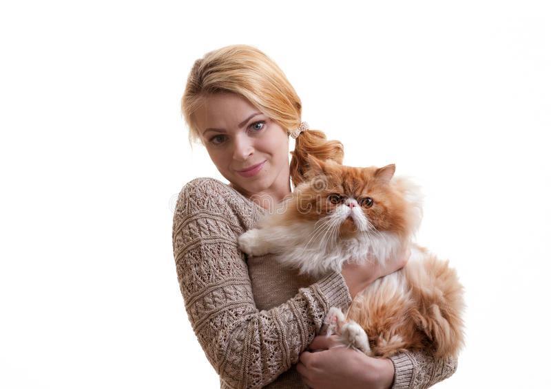 La gentille fille avec un chat rouge sur des mains photo libre de droits