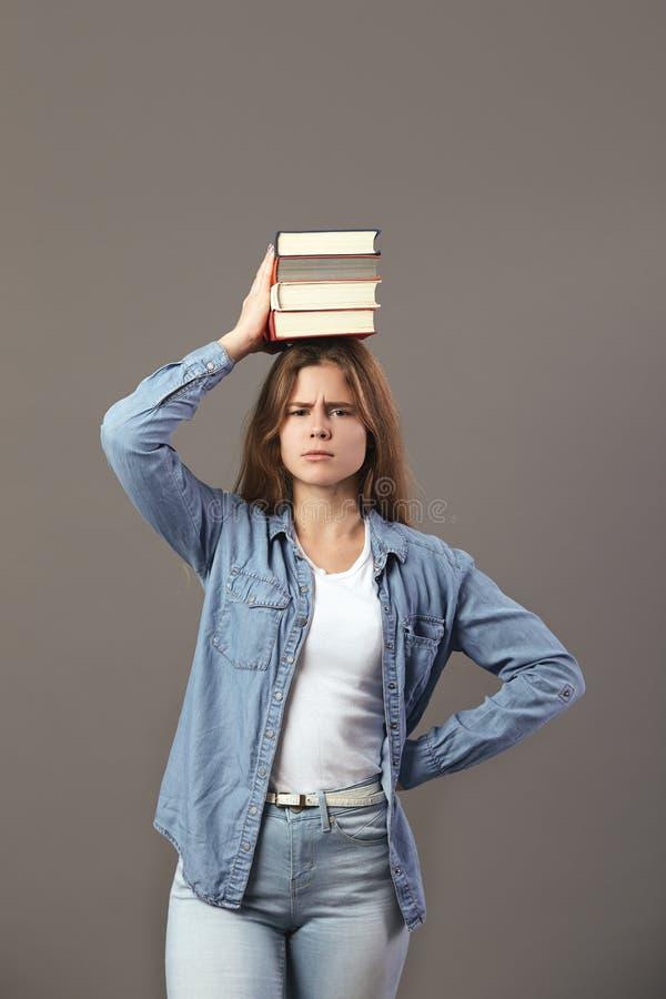 La gentille fille châtain habillée dans un T-shirt blanc, des jeans et des jeans tient des livres sur sa tête sur un fond gris photo libre de droits