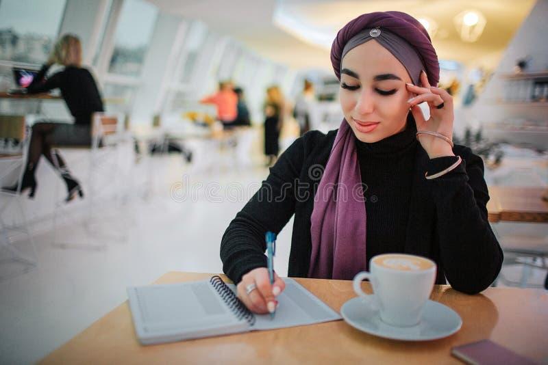 La gentille jeune femme Arabe s'assied à la table intérieure et blanche dans le carnet elle regarde vers le bas Tasse de café ded photo stock