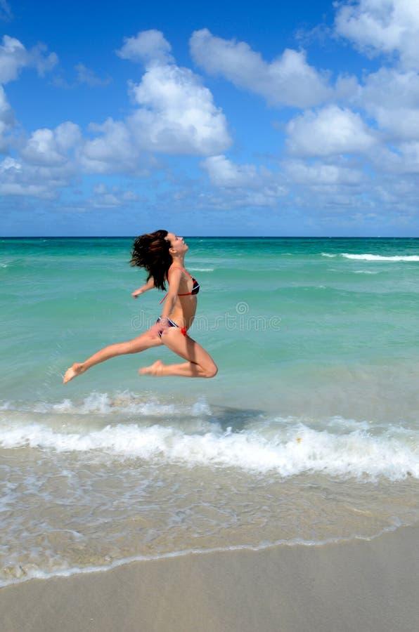 La gentille jeune fille saute près de l'océan photographie stock libre de droits