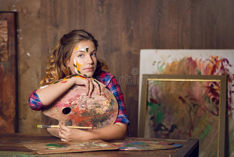 La gentille jolie adolescent-fille étudie dans l'art-studio photo stock