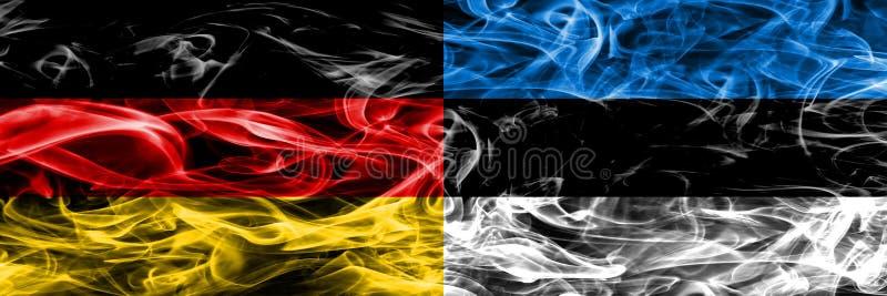 La Germania contro le bandiere del fumo dell'Estonia disposte parallelamente Tedesco ed E immagini stock