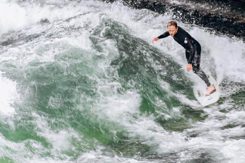 La Germania, Monaco di Baviera - 1° settembre 2013 Uomo sportivo di Atractive nel praticare il surfing shorty del neoprene sull'o fotografie stock libere da diritti