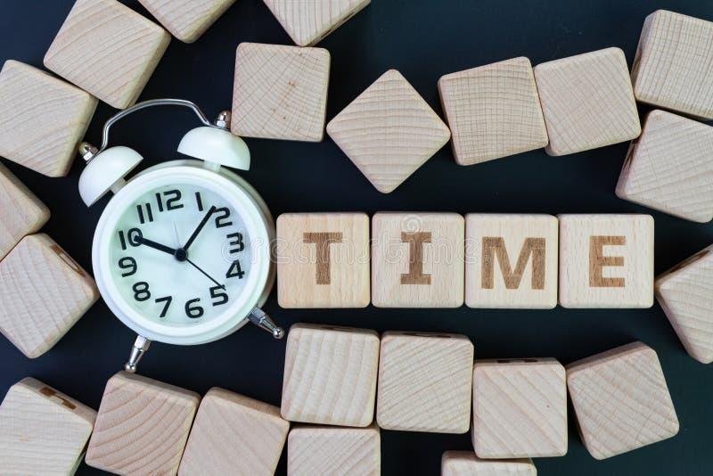 La gestión de tiempo, el plazo, el horario y el concepto del recordatorio, se rezagan los bloques de madera del cubo con alguna c fotos de archivo