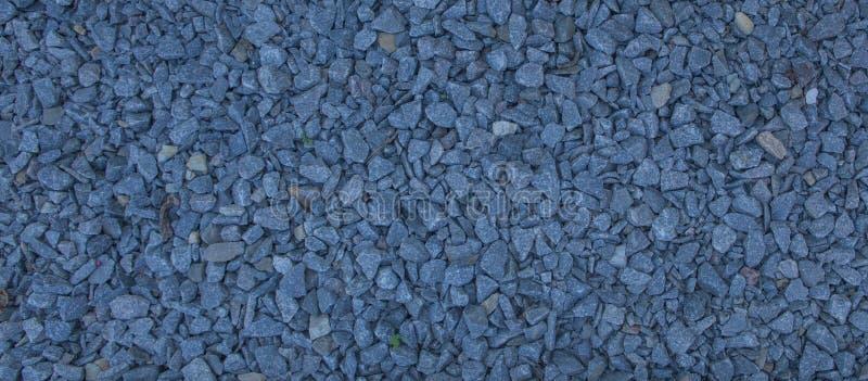 La ghiaia del granito di macadam, oscilla il gray blu schiacciato per costruzione sulla terra, fondo di struttura di ghiaione fotografie stock