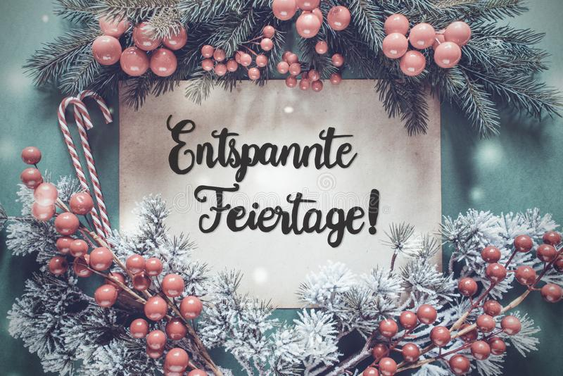 La ghirlanda, calligrafia Entspannte Feiertage significa il Buon Natale fotografia stock libera da diritti