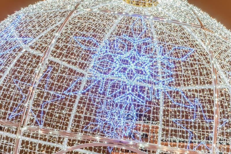 La ghirlanda di Christmass si è arrotolata su una grande struttura sferica d'acciaio fotografia stock libera da diritti