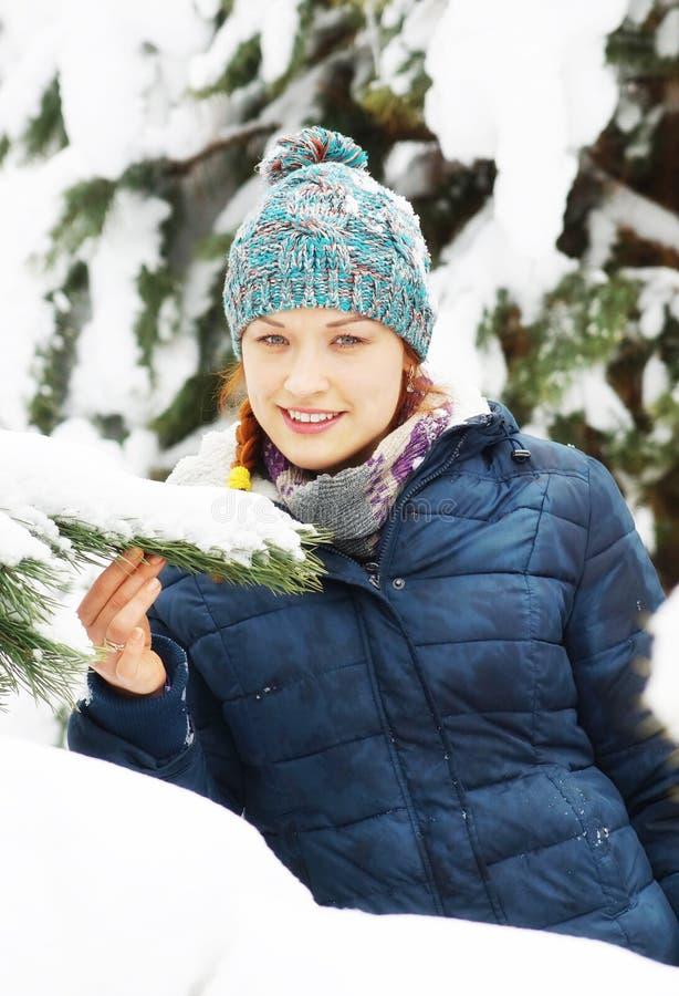 La giacca blu d'uso della bella ragazza gioiosa sta accanto all'albero nevoso fotografia stock