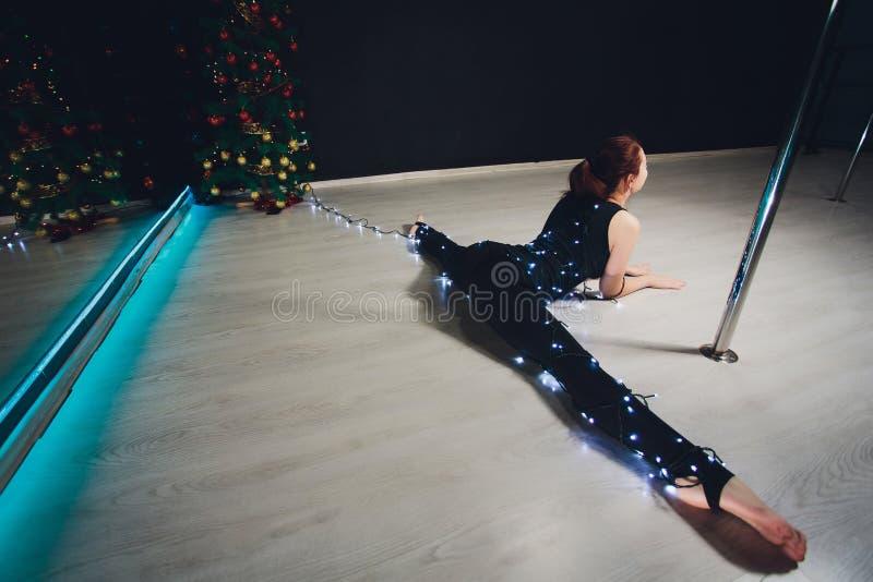 La ginnasta della ragazza la luce delle ghirlande Buona notte immagini stock