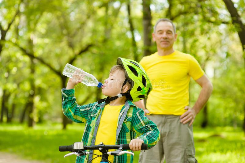 La giovane acqua della bevanda del ragazzo sta imparando guidare una bici con suo nonno fotografie stock libere da diritti
