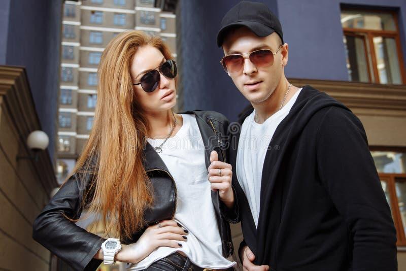 La giovane bella coppia di modo alla moda copre con gli occhiali da sole sulla via fotografia stock