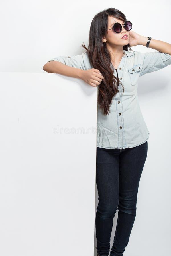 La giovane bella donna asiatica con gli occhiali da sole e tiene un whi in bianco fotografie stock