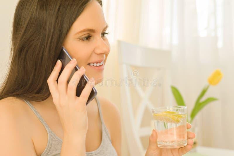 La giovane bella donna beve l'acqua con il limone che si siede a casa a letto, parlando sul telefono cellulare, alimento sano del fotografia stock