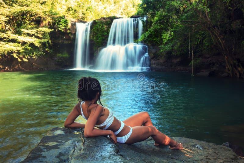 La giovane bella donna in bikini esplora la cascata nascosta nella giungla tropicale sulla natura tropicale selvaggia stupefacent immagine stock