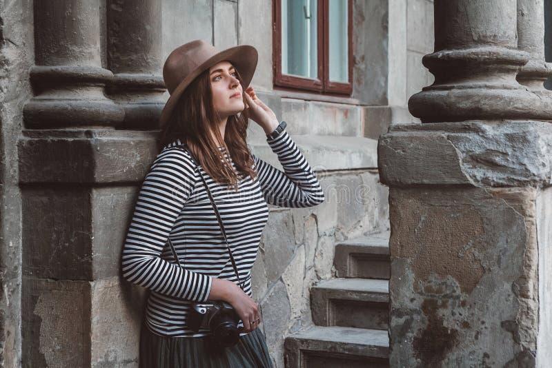 La giovane bella donna in cappello sta prendendo l'immagine con la macchina fotografica antiquata, all'aperto fotografie stock