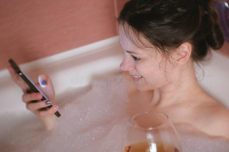 Download La Giovane Bella Donna Castana Prende Un Bagno, Beve Il Whiskey E Scrive Un Messaggio Sul Telefono Cellulare Immagine Stock - Immagine di cura, pulisca: 117981837