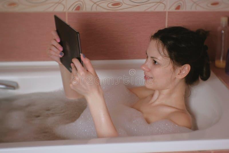 La giovane bella donna castana prende un bagno e guarda il video sulla compressa fotografie stock libere da diritti