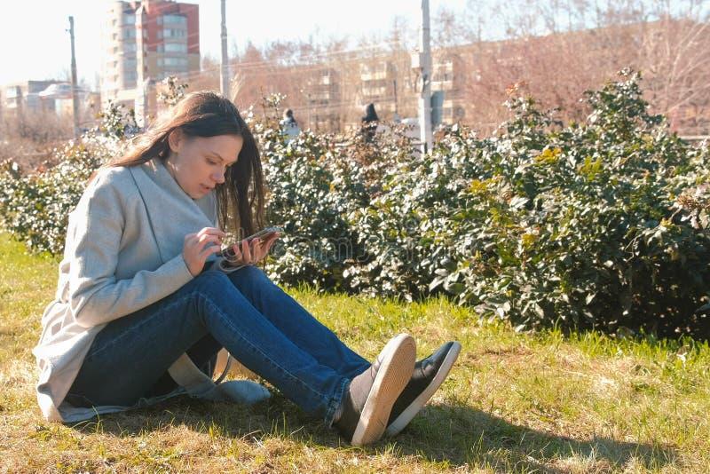La giovane bella donna castana si siede su erba nel parco di primavera, ascolta musica sul telefono e canta una canzone immagini stock libere da diritti