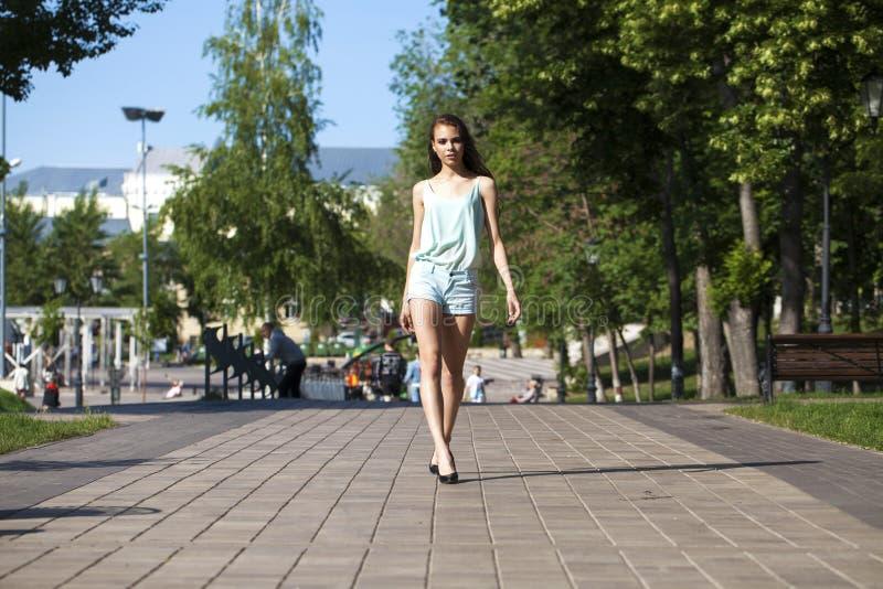 La giovane bella donna castana in una blusa blu e mette la camminata in cortocircuito sulla via fotografia stock libera da diritti