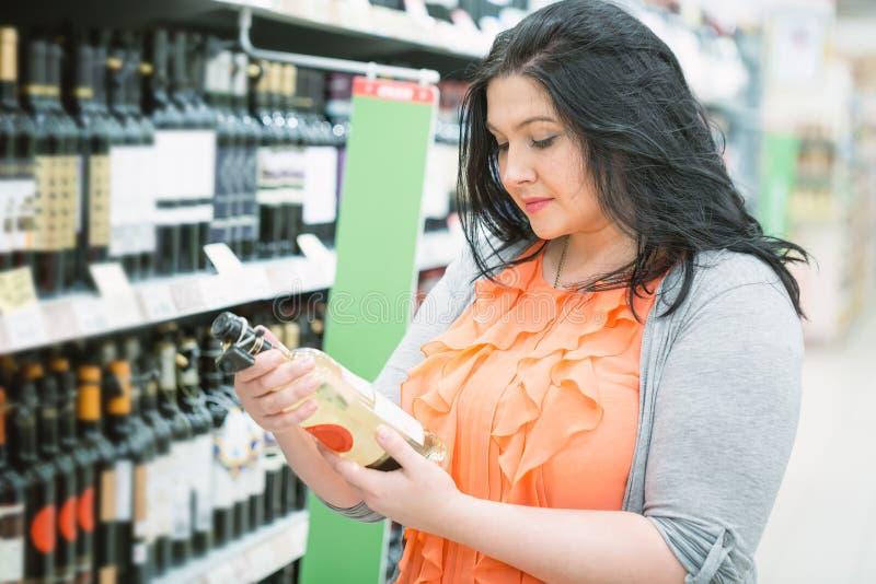 La giovane bella donna caucasica castana sta scegliendo l'alcool del vino nel supermercato Chiuda sul ritratto fotografie stock