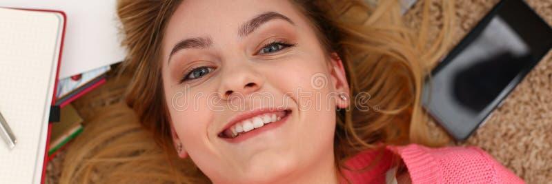 La giovane bella donna che la bugia sul pavimento ha molto lavoro è stanca fotografia stock libera da diritti
