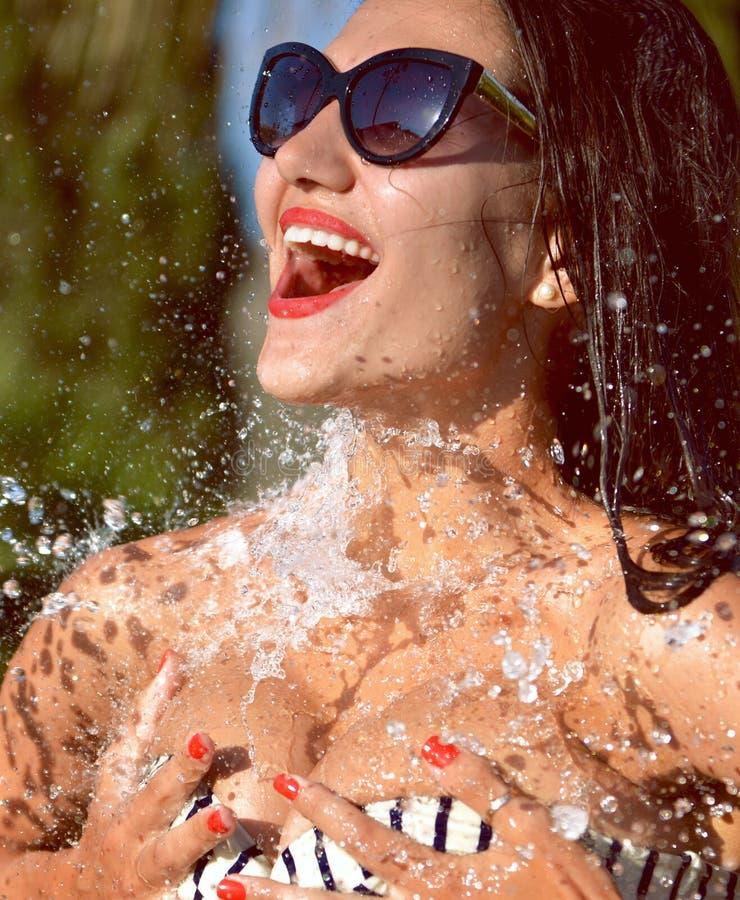 La giovane bella donna con acqua spruzza in occhiali da sole e in biki fotografia stock libera da diritti