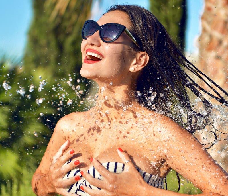 La giovane bella donna con acqua spruzza in occhiali da sole e in biki immagine stock libera da diritti
