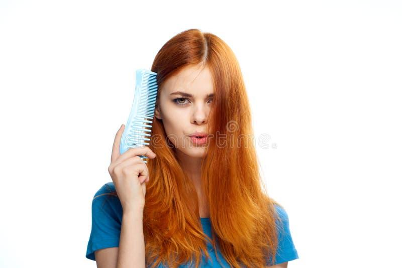 La giovane bella donna con capelli rossi su bianco ha isolato il fondo, il pettine, l'acconciatura, taglio di capelli immagini stock