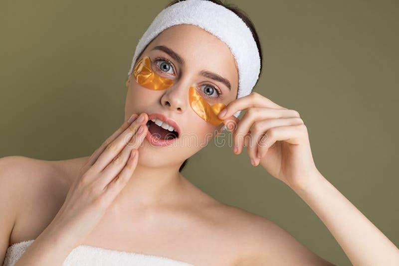 La giovane bella donna con naturale compone l'eliminazione della toppa dell'oro da sotto il suo occhio fotografia stock
