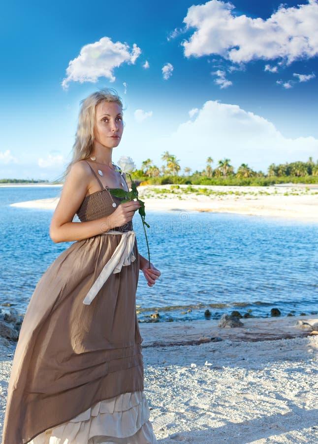 La giovane bella donna con una rosa sul litorale. Ritratto in un giorno soleggiato fotografia stock libera da diritti