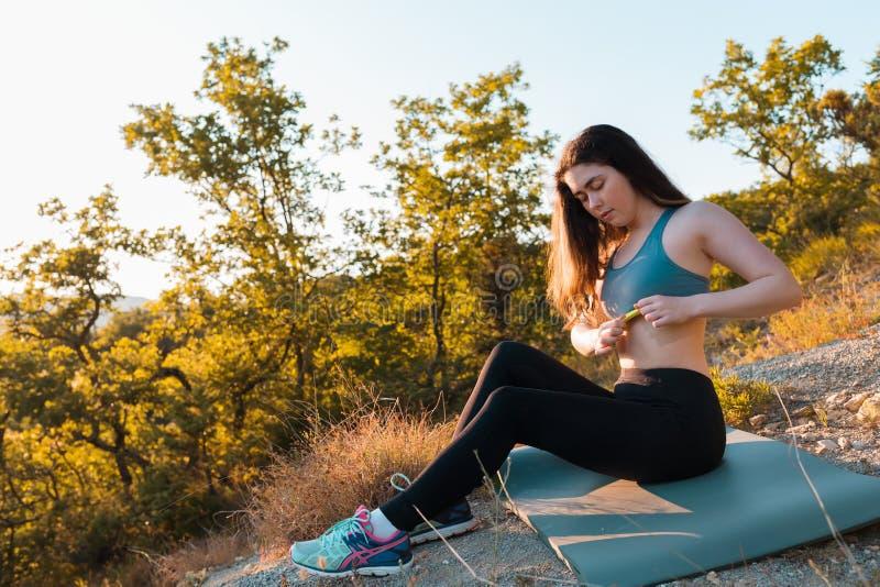 La giovane bella donna corregge l'argomento di sport durante il riscaldamento sulla stuoia Il concetto di yoga, degli sport e del fotografia stock libera da diritti
