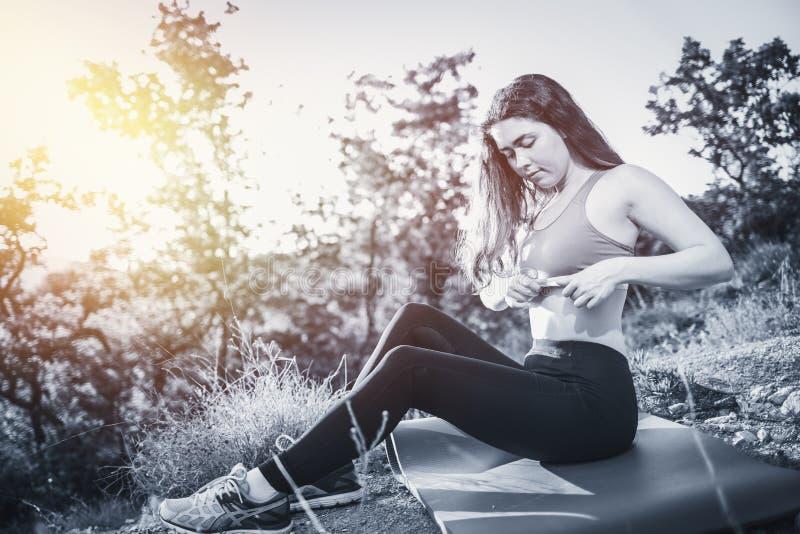 La giovane bella donna corregge l'argomento di sport durante il riscaldamento sulla stuoia Il concetto di yoga, degli sport e del fotografia stock