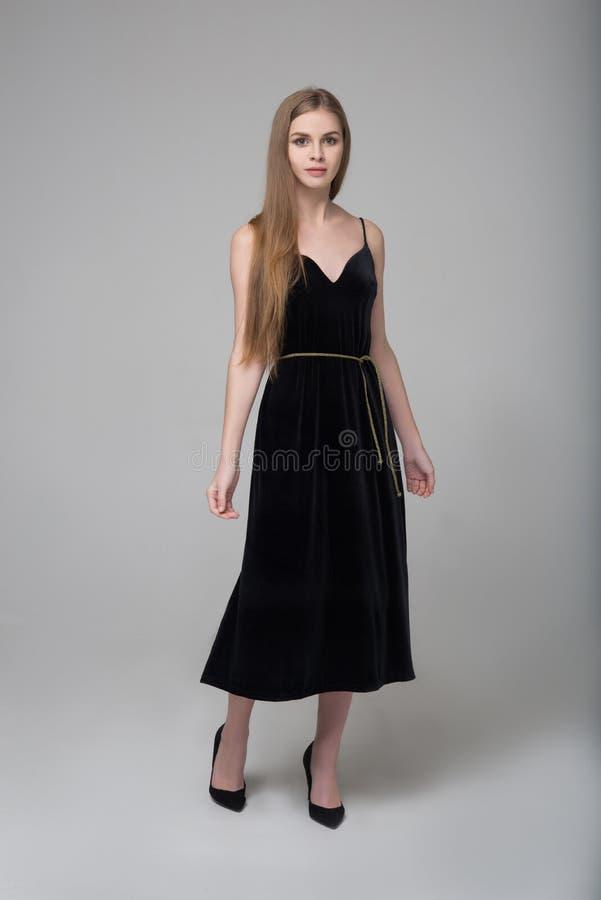 La giovane bella donna dai capelli lunghi posa in vestito nero lungo fotografia stock libera da diritti