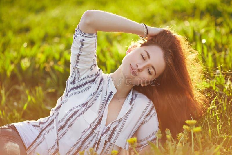 La giovane bella donna della testarossa si siede su un prato verde Chiuda gli occhi immagini stock