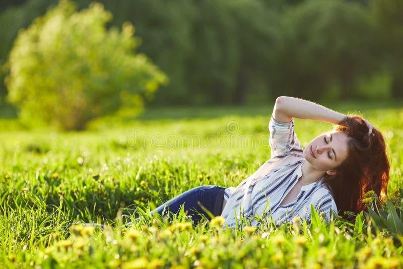 La giovane bella donna della testarossa si siede su un prato verde Chiuda gli occhi immagine stock libera da diritti