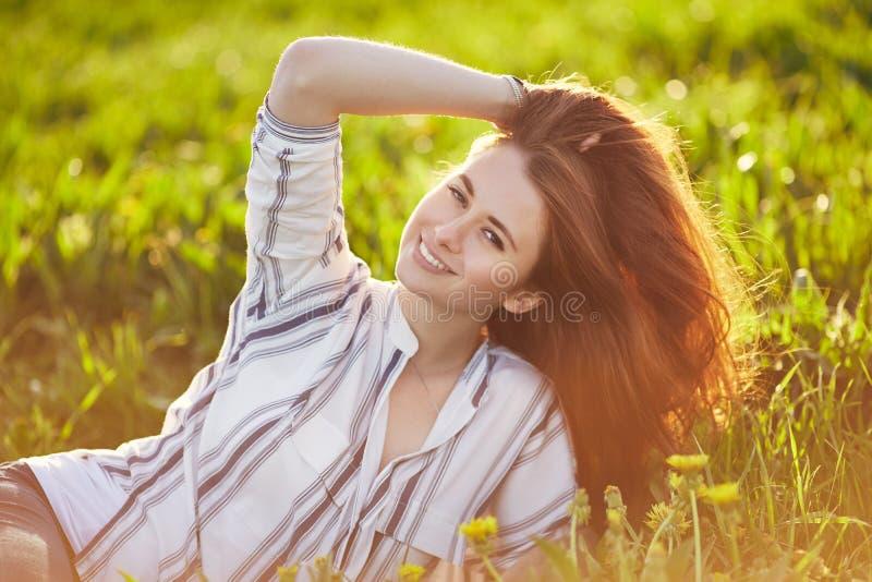 La giovane bella donna della testarossa si siede su un prato verde, esaminante la macchina fotografica fotografia stock