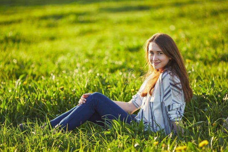 La giovane bella donna della testarossa si siede su un prato verde, esaminante la macchina fotografica fotografia stock libera da diritti