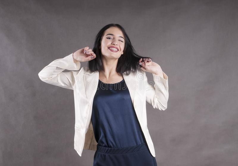 La giovane bella donna di affari felice che sembra l'espressione allegra della positività rinforza lo studio castana immagini stock