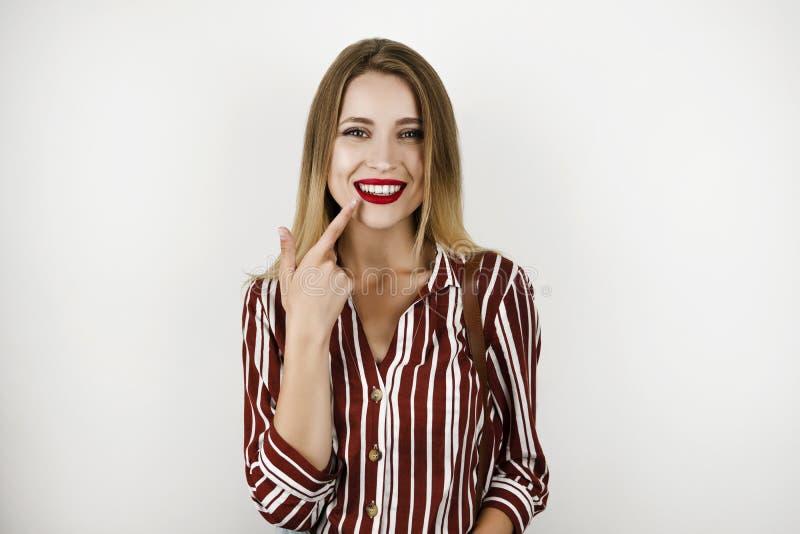 La giovane bella donna di misura della bionda che porta la camicia a strisce d'avanguardia che mostra i denti bianchi sani ha iso fotografie stock