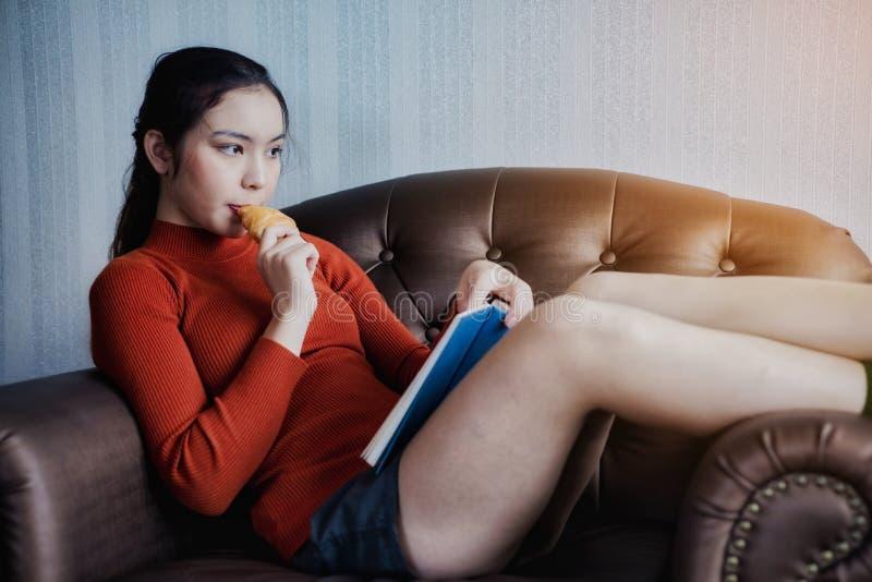 La giovane bella donna ha letto un libro con la prima colazione per la festa di rilassamento fotografia stock