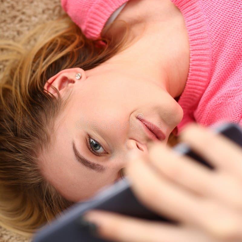 La giovane bella donna ha una bugia di resto sullo smartphone della tenuta del pavimento in armi fotografia stock libera da diritti