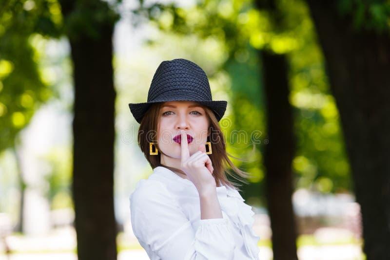 La giovane bella donna nelle manifestazioni del cappello mette a tacere il segno fotografia stock