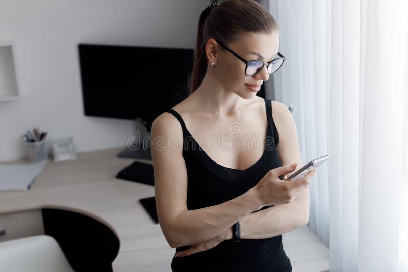 La giovane bella donna passa il tempo a lavorare su un computer che osserva i requisiti della modalità di isolamento durante un'e fotografia stock libera da diritti