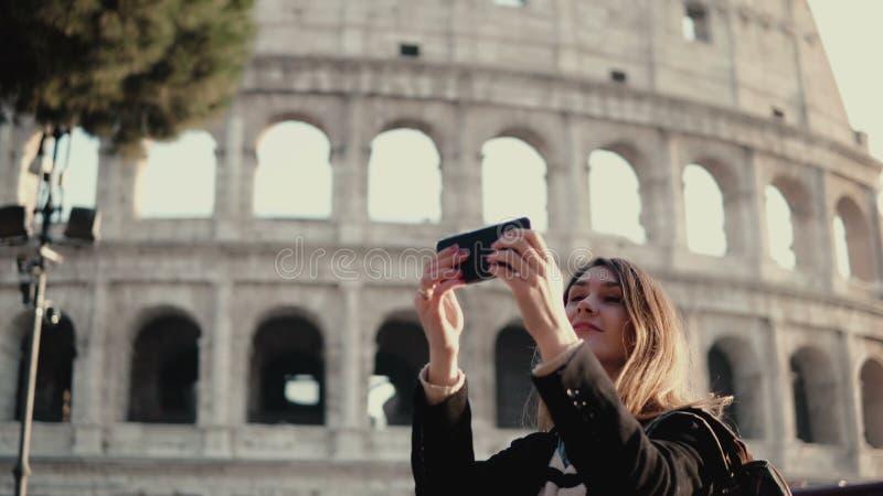 La giovane bella donna prende il selfie sullo smartphone Donna che cammina a Roma, Italia vicino al Colosseum immagine stock