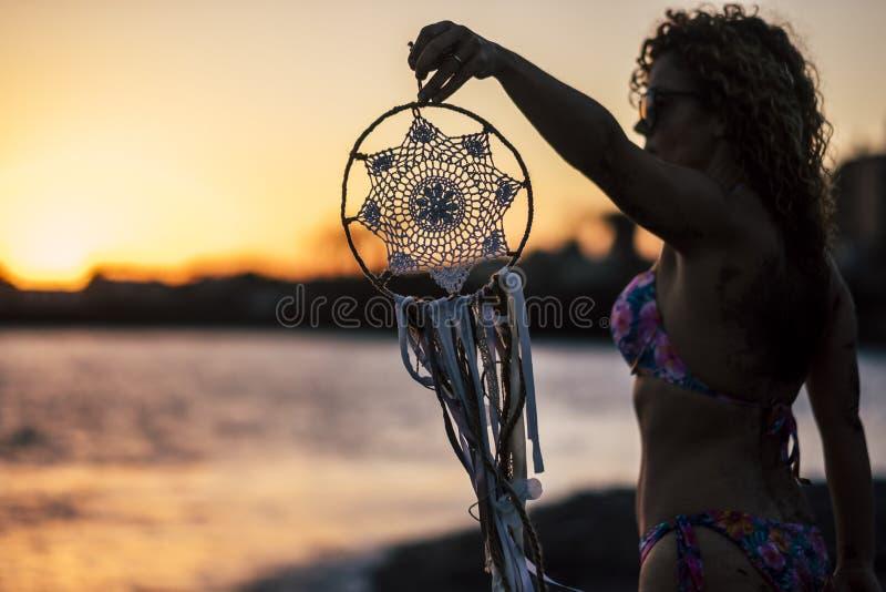 La giovane bella donna prende un dreamcatcher durante il tramonto meraviglioso alla spiaggia davanti all'oceano sensibilità con l fotografia stock