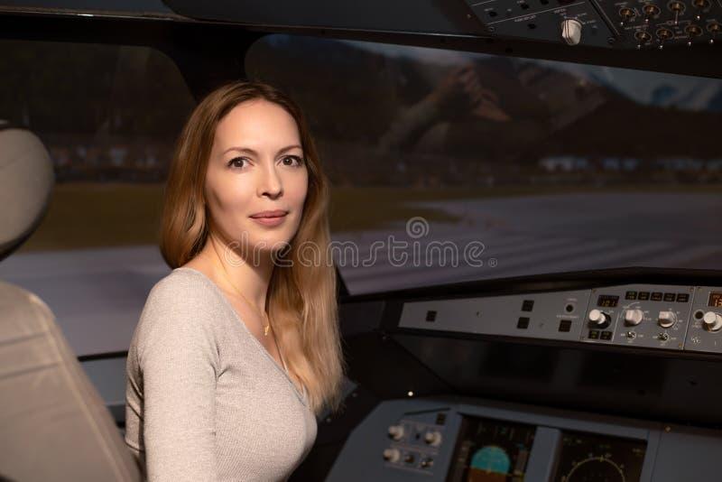 La giovane bella donna si siede sul sedile del pilota nel sedile al timone ed al cruscotto di un aereo dell'aereo di linea fotografia stock