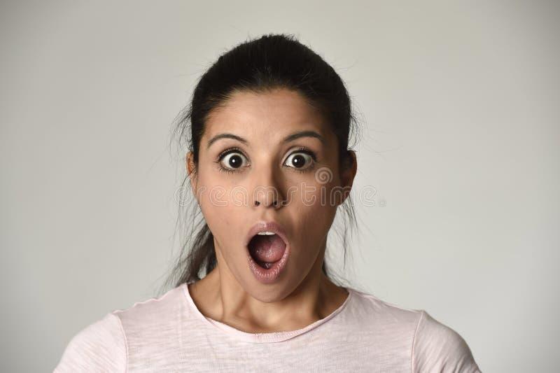 La giovane bella donna sorpresa ha stupito nella scossa e nella sorpresa con grande della bocca aperto fotografia stock libera da diritti
