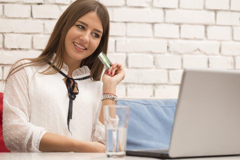 La giovane bella donna sorridente si siede ad una tavola e compra online immagini stock libere da diritti